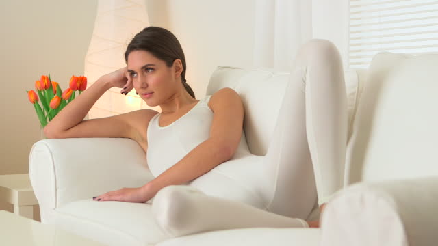 Elegant woman lying on couch in white singlet