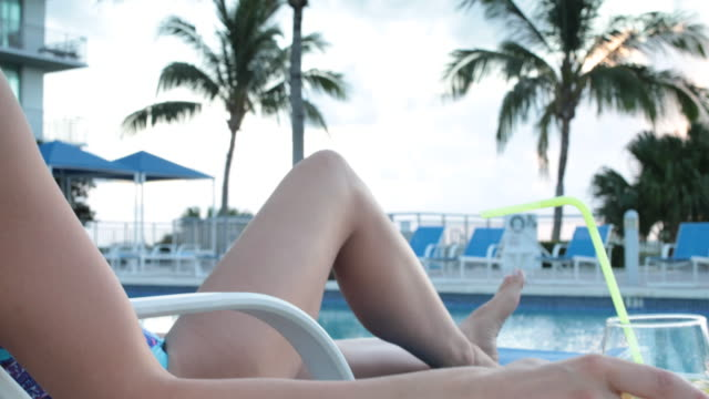 CU Elegant woman reaching out and grasping a drink on table beside sunlounger