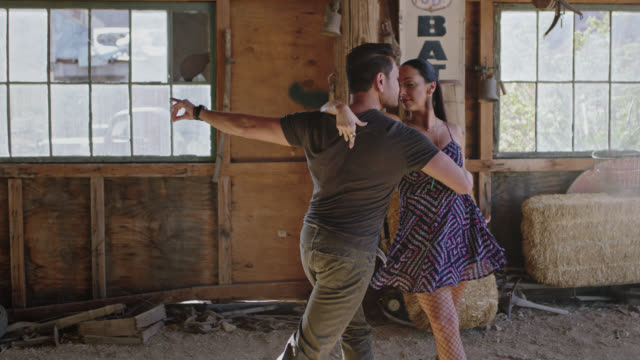 Elegant woman stares at camera and dances with partner on sawdust floor of rustic barn.