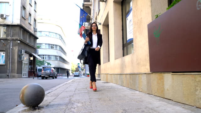 vídeos de stock e filmes b-roll de elegant woman walking on the street with clip folder in hand - pasta