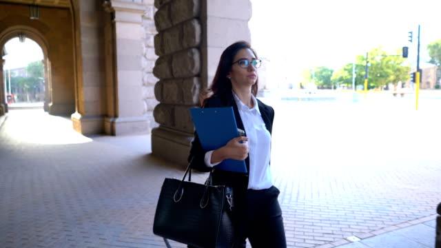Elegante Frau, die unter dem Gebäude-Bogen mit Clip-Ordner in der hand.