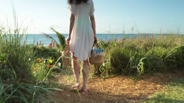 ts ws elegant woman walks along path towards the sea, rear view. - beach bag stock videos and b-roll footage