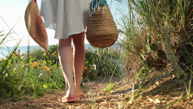 elegant woman walks in to shot along path towards the sea, rear view. - beach bag stock videos and b-roll footage