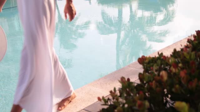 Elegant woman wearing white dress walking carefully on pool edge