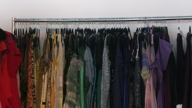 elegant woman's clothes hang on a wardrobe rack. - rack stock videos & royalty-free footage