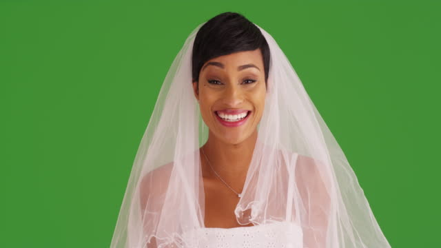 elegant young bride in wedding dress and veil, smiling at camera on green screen - bride 個影片檔及 b 捲影像