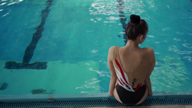 elegant young female swimmer sitting in poolside - woman swimming costume stock videos & royalty-free footage