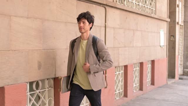 stockvideo's en b-roll-footage met elegante jonge die met skateboard in de hand loopt - driekwartlengte