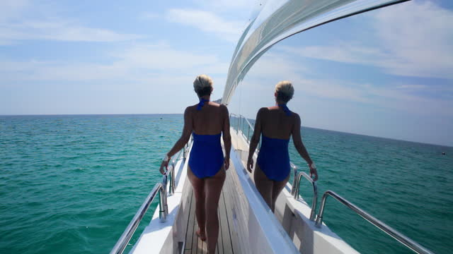 elegant young woman on walking along the side of a luxury yacht. - majorca stock videos & royalty-free footage