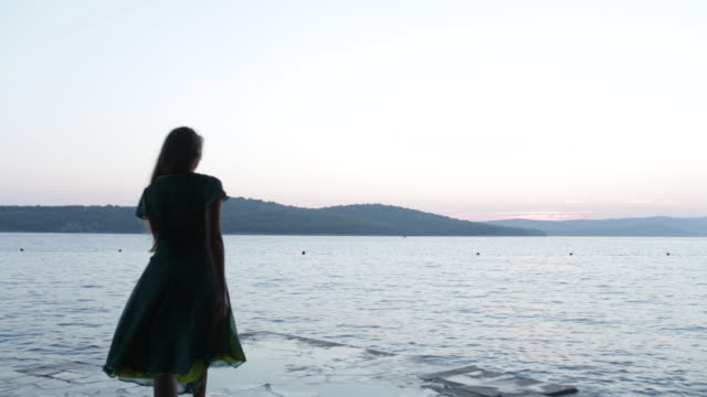 elegant young woman wearing silk dress walks to edge of jetty, she stands on tip toe and looks out to sea. - 手をかざす点の映像素材/bロール