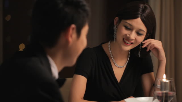 MS Elegantly dressed couple talking during candle lit dinner / China