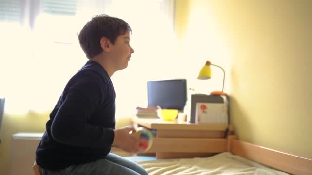 vidéos et rushes de garçon d'âge élémentaire jouant avec la petite bille dans la chambre à coucher - ball