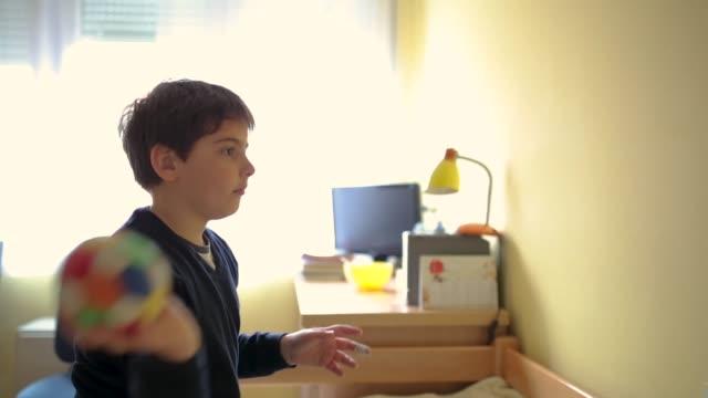 小学生の少年は、寝室で小さなボールで遊んで - 10歳から11歳点の映像素材/bロール