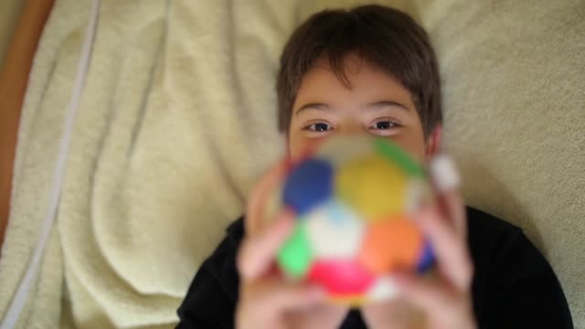 elementary age boy playing with small ball in bedroom while lying on bed - pre adolescent child stock videos & royalty-free footage
