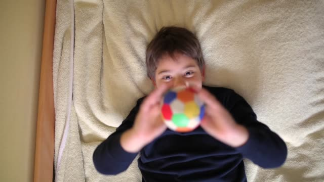 elementary age boy playing with small ball in bedroom while lying on bed - toy stock videos & royalty-free footage