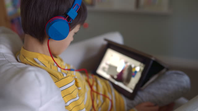 elementary age boy using tablet computer to attend online class - digital native stock videos & royalty-free footage