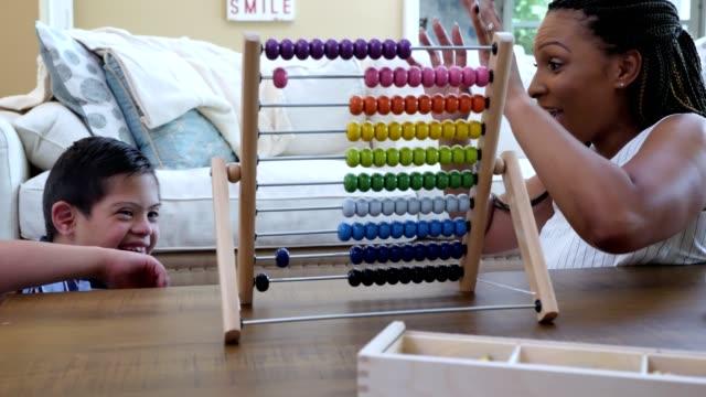 vídeos de stock, filmes e b-roll de o menino elementar da idade com síndrome de down aprecia a terapia do jogo - conta artigo de armarinho