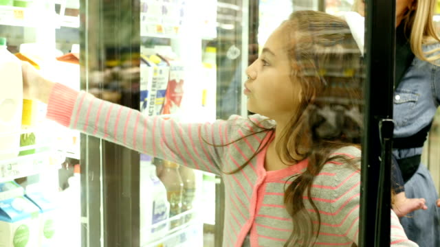 Elementary age child helps Caucasian mid-adult mother shop in the dairy section of local supermarket