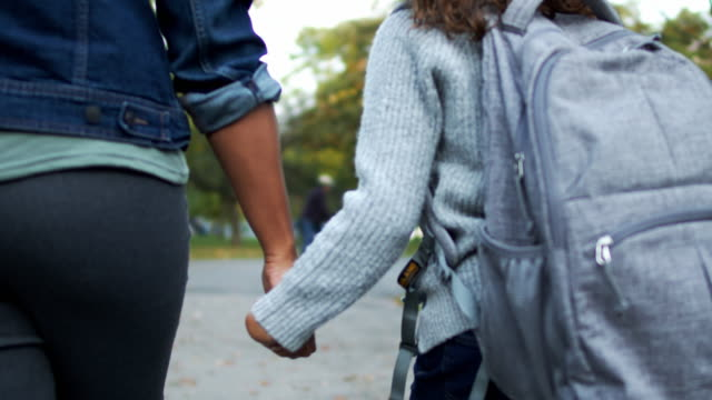 vídeos de stock e filmes b-roll de elementary age girl holding her mother's hand while walking home from school - mochila saco