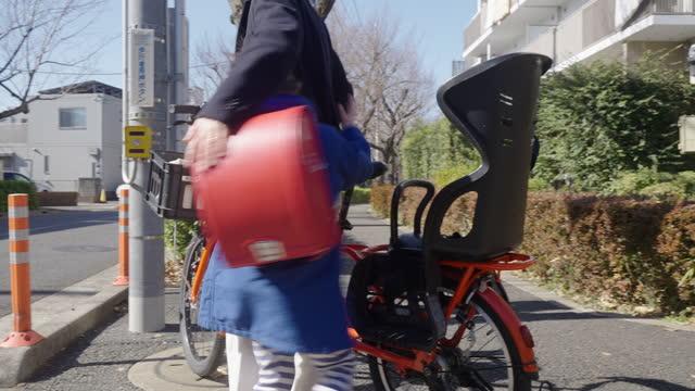 母親に戻って走る初等年齢の女の子 - 新学期点の映像素材/bロール