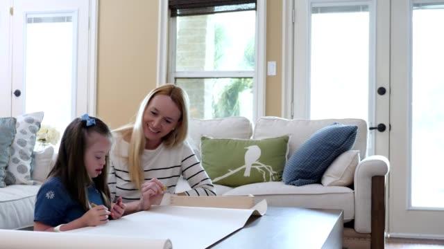 vídeos de stock, filmes e b-roll de menina elementar da idade com para baixo cores da síndrome com sua mamã - mãe solteira