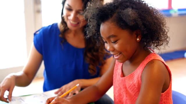 vídeos de stock, filmes e b-roll de garota de idade elementar funciona em problemas de matemática com a professora da creche - professor