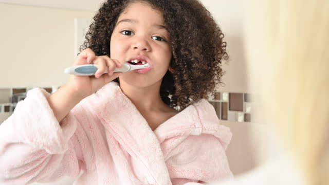 elementary age mixed race girl brushing her teeth - domestic bathroom stock videos & royalty-free footage