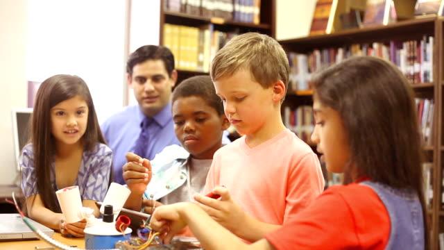 grundschulkind schulmädchen bauen roboter technologie-klasse. - nur mädchen stock-videos und b-roll-filmmaterial