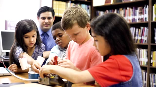 Elementary age school stucents build robot in technology class.