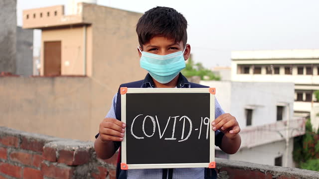 elementary age schoolboy covering his face with pollution mask for protection from viruses and holding chalkboard (writing slate) in hand - 8 9 years stock videos & royalty-free footage