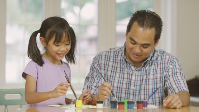 vídeos de stock, filmes e b-roll de elementar envelhecido garota fazendo obras de arte e artesanato com seu pai homeschooling - filipino