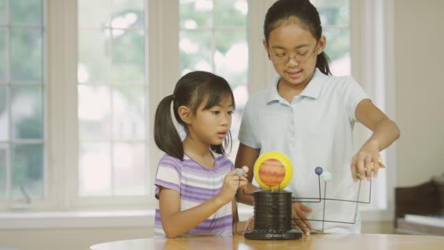 Elementära äldre systrar studerar astronomi medan hem skolgång