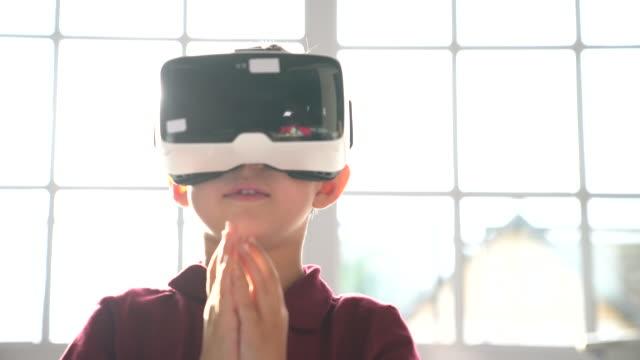 stockvideo's en b-roll-footage met elementaire jongen virtual reality headset te kijken - interactief