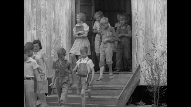 Elementary children exiting school barn MS Children w/ books down steps of barn barefoot in overalls Poor uneducated inadequate Poverty American South