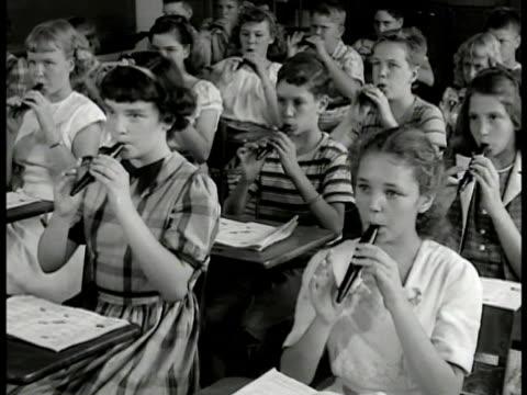elementary children in class room at desk playing tonettes, teacher conducting fg . children playing tonettes. boy playing. teacher conducting w/... - lärarinna bildbanksvideor och videomaterial från bakom kulisserna