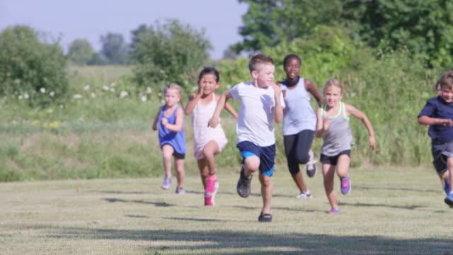 Elementales niños corriendo al aire libre