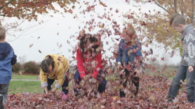 Grundschule Kinder werfen Herbstlaub in der Luft