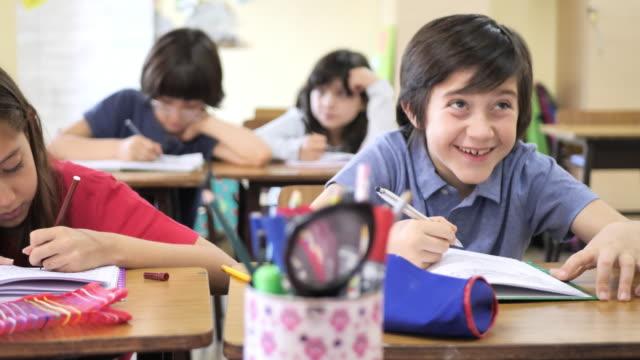 grundutbildning i latinamerika - elever som skriver i sina anteckningsböcker i klassrummet - 6 7 år bildbanksvideor och videomaterial från bakom kulisserna