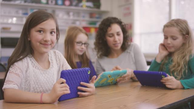 vídeos y material grabado en eventos de stock de escuela primaria de niños trabajan en medios digitales comprimidos con el profesor en clase - niño de escuela primaria