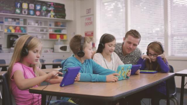 vídeos y material grabado en eventos de stock de escuela primaria de niños trabajan en medios digitales comprimidos con el profesor en clase - niño de primaria