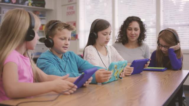 stockvideo's en b-roll-footage met basisschool leeftijd kinderen werken op digitale media tabletten met leraar in de klas - fatcamera