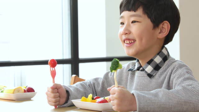 elementary school boy  smiling big with vegetables in two hands - leaf vegetable stock videos & royalty-free footage