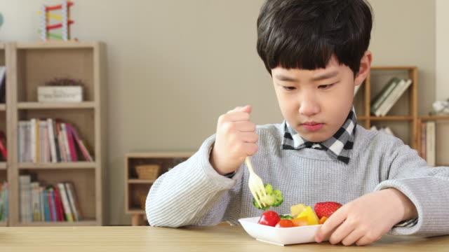 elementary school boy who dislikes vegetable - nur jungen stock-videos und b-roll-filmmaterial