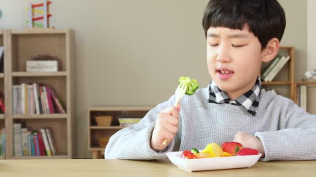elementary school boy who dislikes vegetable - ekel stock-videos und b-roll-filmmaterial