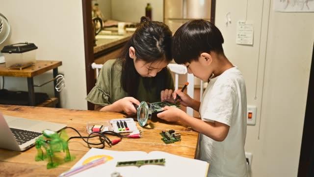 vídeos y material grabado en eventos de stock de niños y niñas de la escuela primaria que trabajan en la codificación y la robótica - lupa