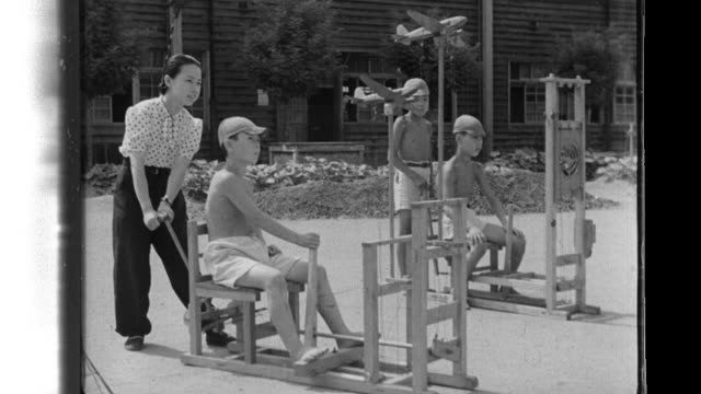 Elementary school boys receiving basic training at their schoolyard to fly a plane blindfolded boys practicing turning chairs they are seated on or...