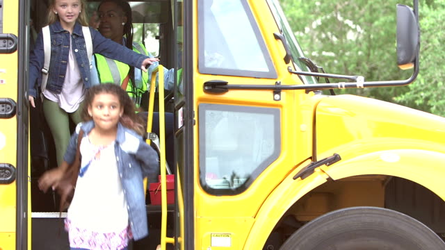 elementary school children exit school bus - educazione video stock e b–roll