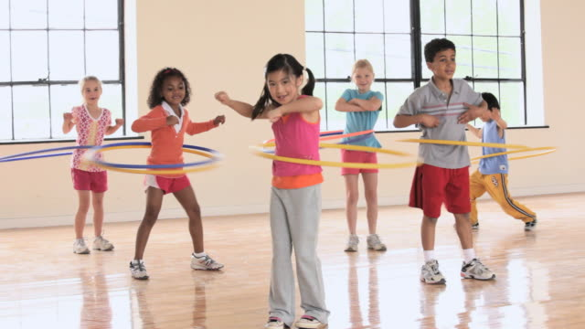 ws pan elementary school children hula hooping in gym / richmond, virginia, united states     - primary age child stock videos and b-roll footage