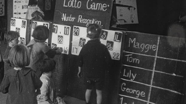 1925 montage elementary school children in classroom playing games including a numbers recognition game based on lotto and subtraction game involving numbers set around a wheel / newcastle upon tyne, england, united kingdom - 1925 stock videos & royalty-free footage