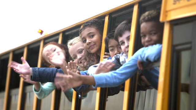 Elementary school children looking out bus window waving